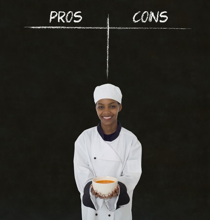 pros: african american woman chef holding soup bowl with chalk pros and cons on blackboard background Stock Photo