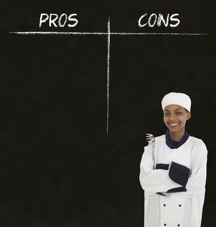 pros: african american woman chef holding utensil with chalk pros and cons on blackboard background Stock Photo