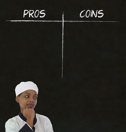 african american woman chef thinking with chalk pros and cons on blackboard background photo