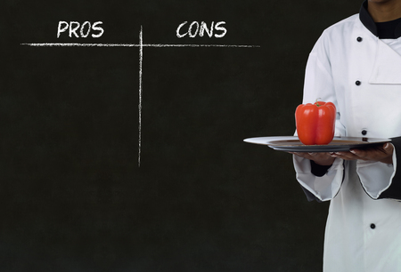 african american chef holding healthy food with chalk pros and cons on blackboard background photo