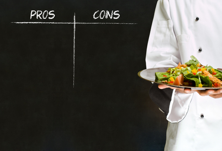 african american woman chef with chalk pros and cons on blackboard background photo