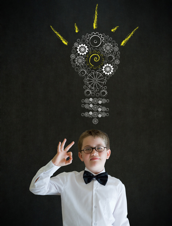all ok: All ok or okay sign boy dressed up as business man with bright idea gear cog lightbulb on blackboard background