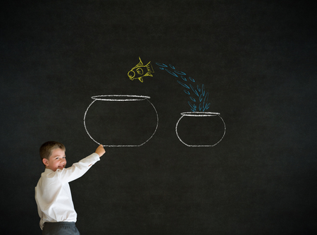 Writing boy dressed up as business man with chalk fish jumping from small bowl to big bowl on blackboard background photo