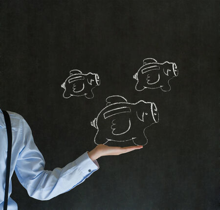 Businessman holding out hand with flying money piggy banks in chalk on blackboard background photo