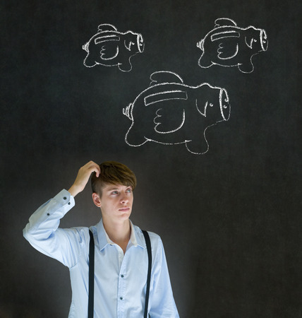 Businessman scratching head with flying money piggy banks in chalk on blackboard background photo