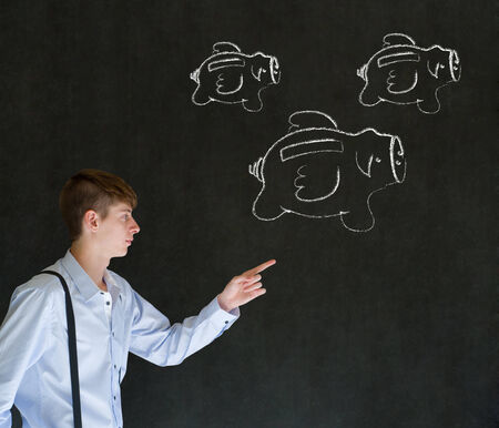 Businessman pointing at flying money piggy banks in chalk on blackboard background photo