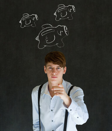 Businessman pointing with flying money piggy banks in chalk on blackboard background photo