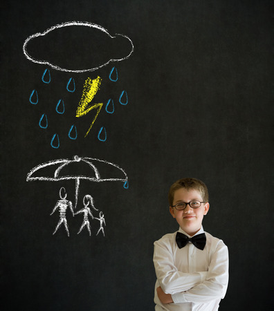 Thinking boy dressed up as business man thinking about protecting family from natural disaster on blackboard background photo