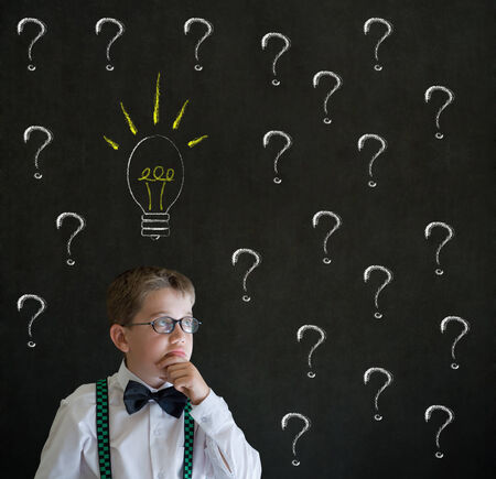 thinks: Thinking boy dressed up as business man questioning ideas on blackboard background Stock Photo