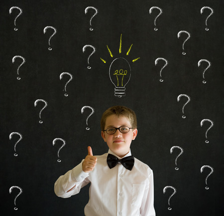 child looking up: Thumbs up boy dressed up as business man questioning ideas on blackboard background