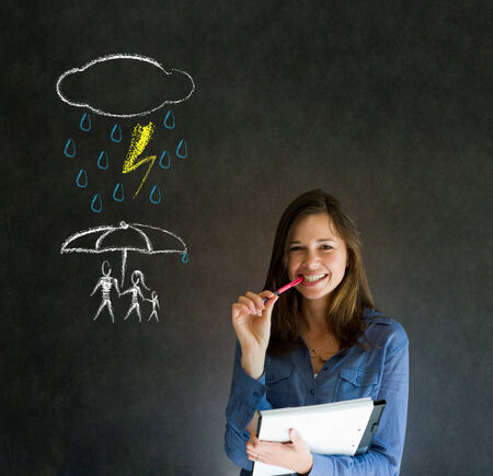 Woman Teacher thinking about protecting family from natural disaster on blackboard background Stock Photo