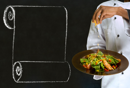 African America chef holding health salad dish with chalk scroll on blackboard Background photo