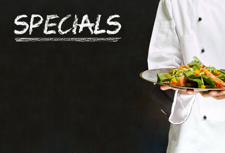 specials: African American woman chef with chalk specials sign on blackboard background