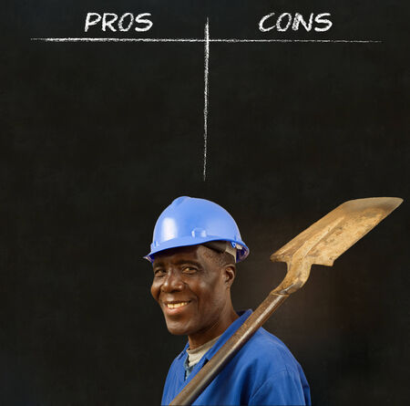 cons: African American black man worker with chalk pros and cons decision list on a blackboard background