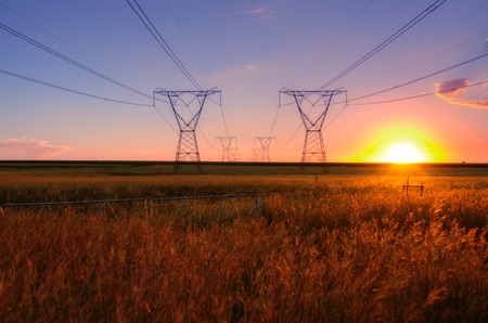 South African electricity power lines with sun at dusk on the highveld  Stock Photo