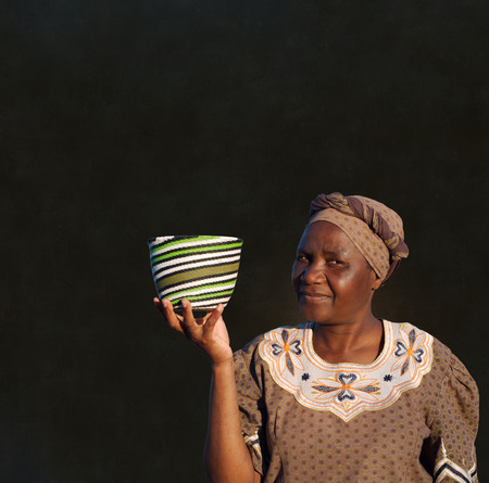 businessowman: Traditional South African Zulu woman basket sales woman on blackboard background