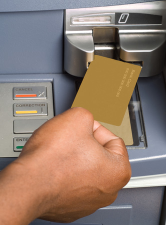 South African or African American drawing cash money with bank ATM card in auto teller machine photo