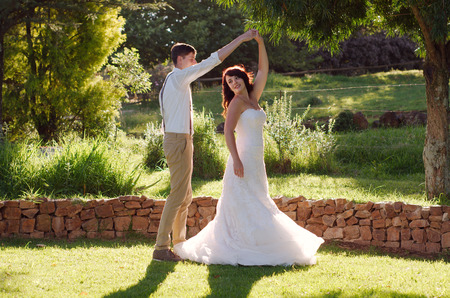 newly wedded couple: Bride and groom dancing outside garden wedding ceremony