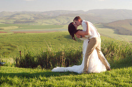 africa kiss: Bride and groom outside garden wedding with African Natal Midlands mountain scenery background