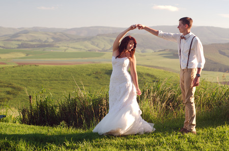 Bride and groom outside garden wedding with African Natal Midlands mountain scenery background photo