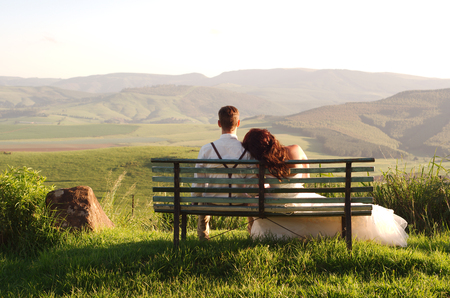garden scenery: Bride and groom outside garden wedding on bench with African Natal Midlands mountain scenery background