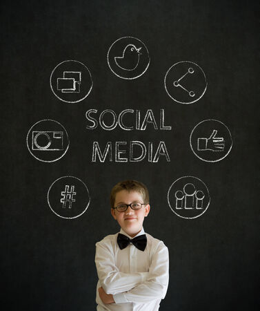Thinking boy dressed up as business man with social media icons on blackboard background photo