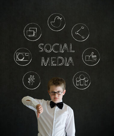 Thumbs down boy dressed up as business man with social media icons on blackboard background photo