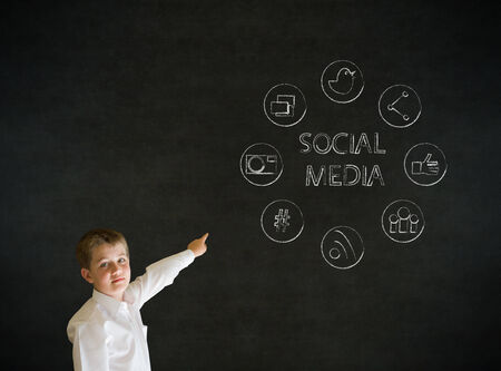 Pointing boy dressed up as business man with social media icons on blackboard background photo