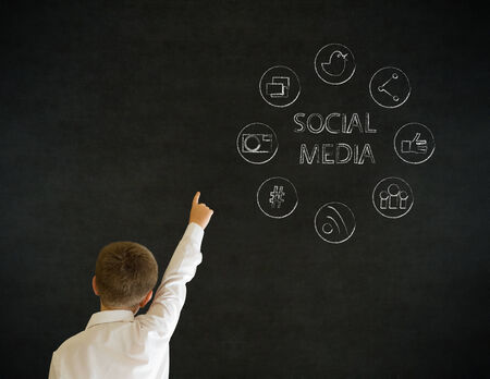Hand up answer boy dressed up as business man with social media icons on blackboard background photo