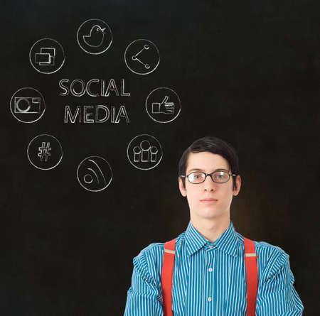 Nerd geek businessman with computer social media network icons on blackboard background