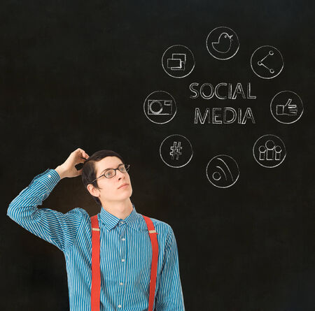 Nerd geek businessman with computer social media network icons on blackboard background photo