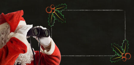 christmas promotion: Father Christmas looking at the future sales strategy notes with binoculars on backboard background