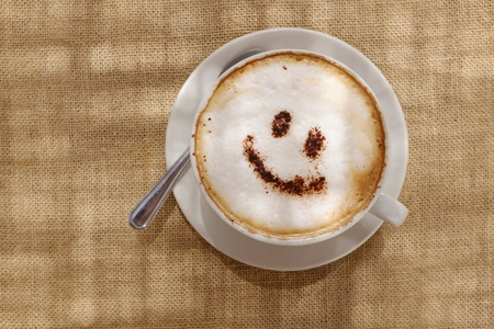 Coffee cappuccino with foam or chocolate smiling welcome happy face in restaurant or hotel