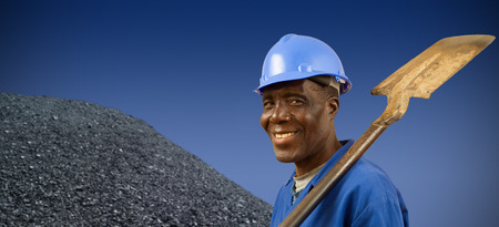 South African or African American coal miner with coal pile