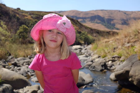 Young child or girl on holiday relaxing at South African Drakensburg mountain stream or river photo