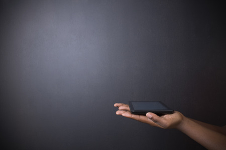 american media: South African or African American woman teacher or student holding computer tablet on blackboard background