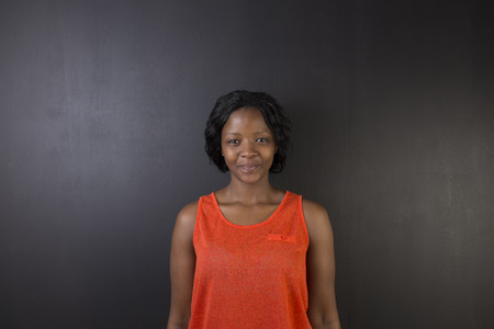american content: South African or African American woman teacher or student against a dark blackboard background