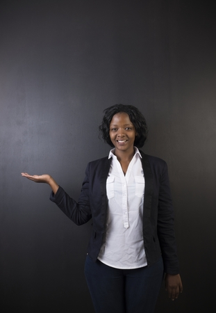 woman black background: South African or African American woman teacher or student with hand out on chalk black board background