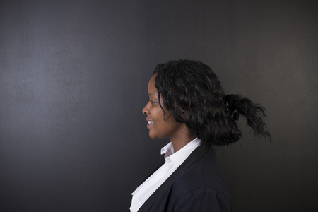 woman black background: South African or African American woman teacher on chalk black board background