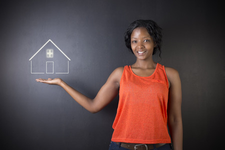 sell: South African or African American woman teacher, student, saleswoman or businesswoman against black background holding house, home or real estate Stock Photo