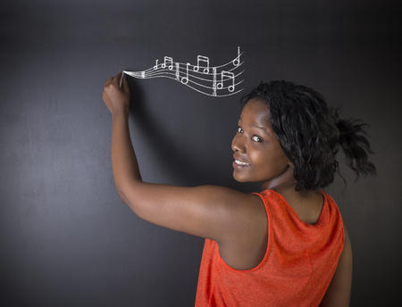 teaching music: Learn music South African or African American woman teacher or student with chalk music notes blackboard background