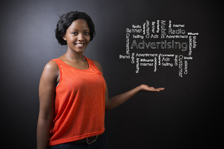 South African or African American woman teacher or student against blackboard background with chalk advertising diagram photo