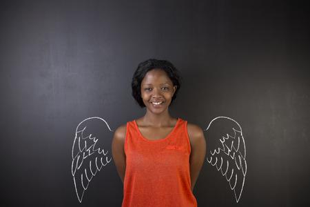 angel de la guarda: Sudáfrica o africano profesora o estudiante ángel americano con alas de tiza en fondo de la pizarra Foto de archivo