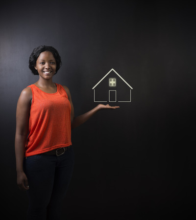 tenant: South African or African American woman teacher, student, saleswoman or businesswoman against black background holding house, home or real estate Stock Photo