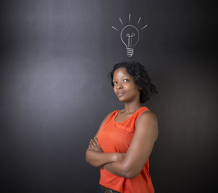 african business woman: Bright idea chalk background lightbulb thinking South African or African American woman teacher or student Stock Photo