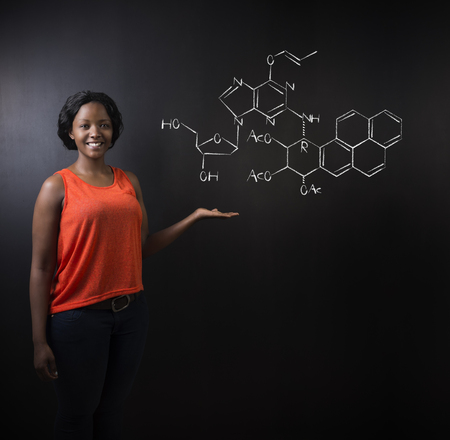 science lesson: Learn science or chemistry formula confident beautiful South African or African American woman teacher or student chalk blackboard background