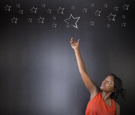 South African or African American woman teacher or student reaching for the stars success against blackboard background Standard-Bild