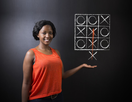 Thinking out of the box South African or African American woman teacher or student tic tac toe on blackboard background photo