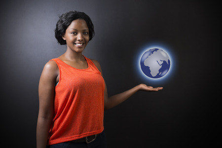 South African or African American woman teacher or student holding world earth globe in the palm of her had on black background photo