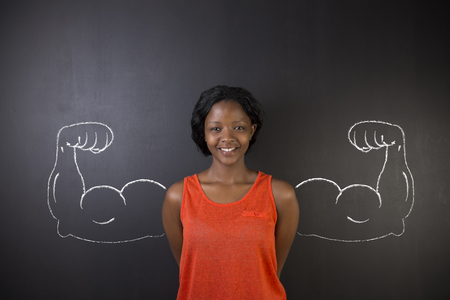 South African or African American woman teacher with healthy strong arm muscles for success on blackboard background